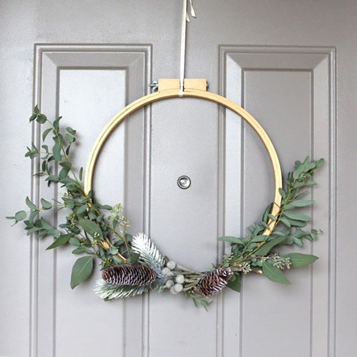 Creative door decor with embroidery hoop, green leaves and pine-cones.