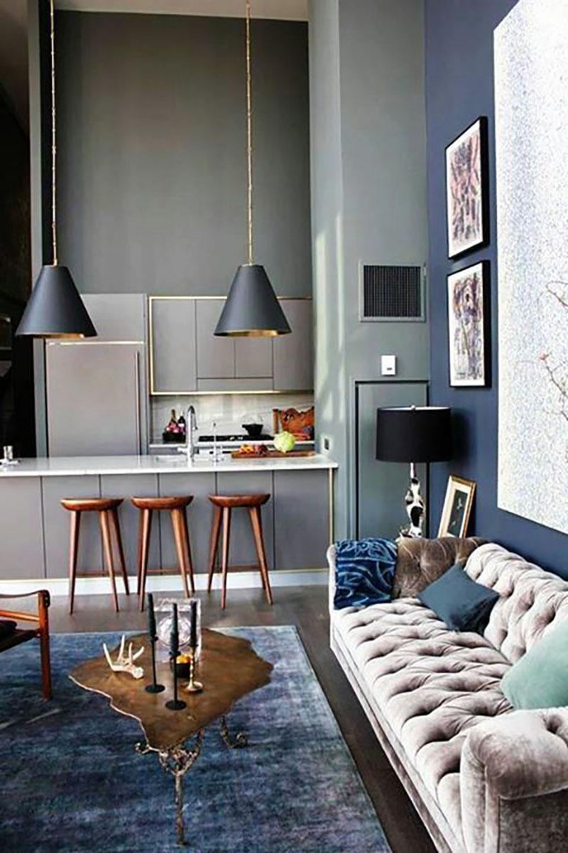 Kék fal, szürke konyha, kék szőnyeg egy világos kanapéval, hozzá sötét szürke lámpák.