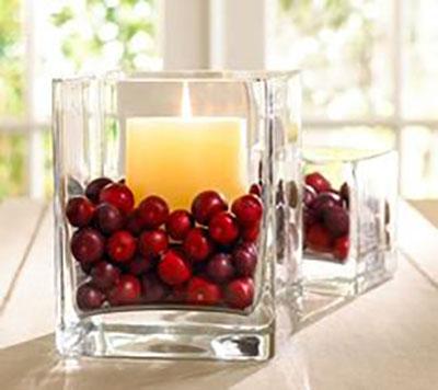 Piros bogyók fehér gyertyával üveg vázában, ez is egyszerűen nagyszerű.