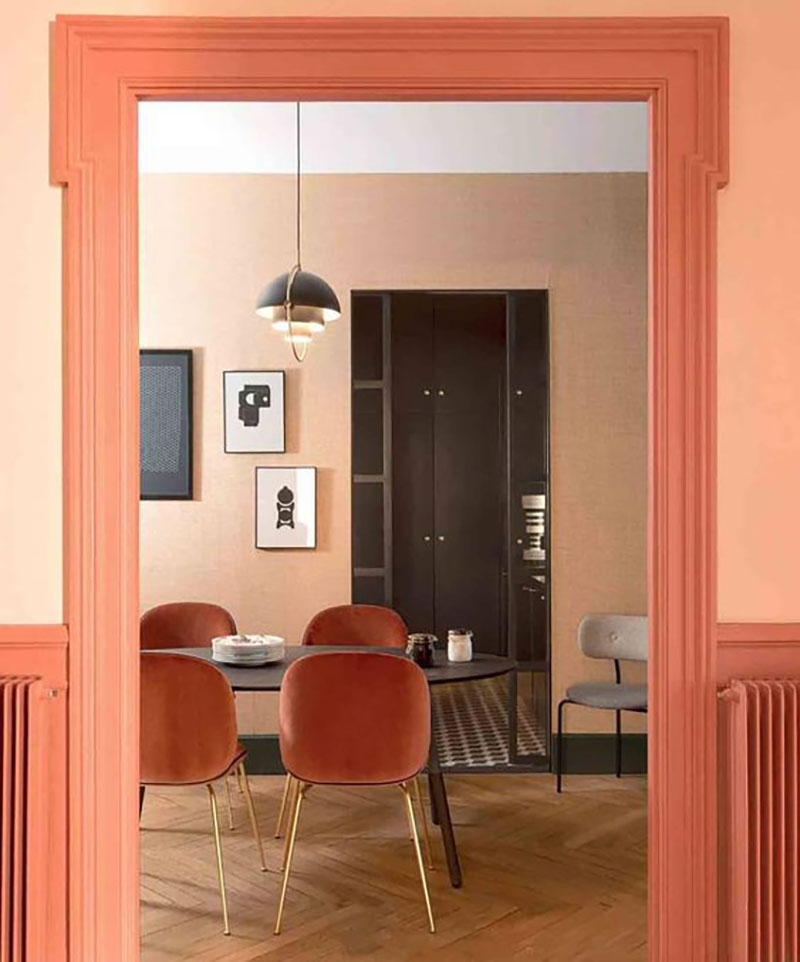 The shades of peach on the wall look great, plus the peach-colored dining chairs on golden legs.