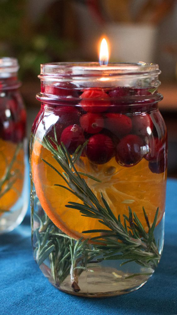 Take a jar, some rosemary branches, orange slices and some red berries. Pour some water on it and put the floating candle to the top.