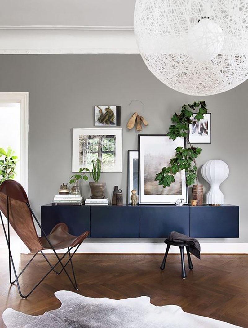 Szürke fal és kék nappali bútor, szürkés állatbőr szőnyeggel, nagyon jól néz ki a sok kép is a falon és a falnak támasztva.
