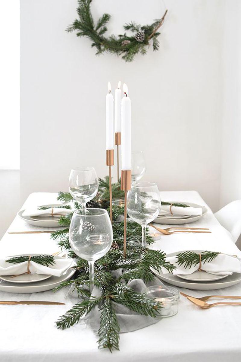 Talán ennél egyszerűbb nem is lehetne, fehér teríték arannyal kombinálva és zöld fenyőfa ágacskák. Éppen az egyszerűsége miatt letisztult és gyönyörű.