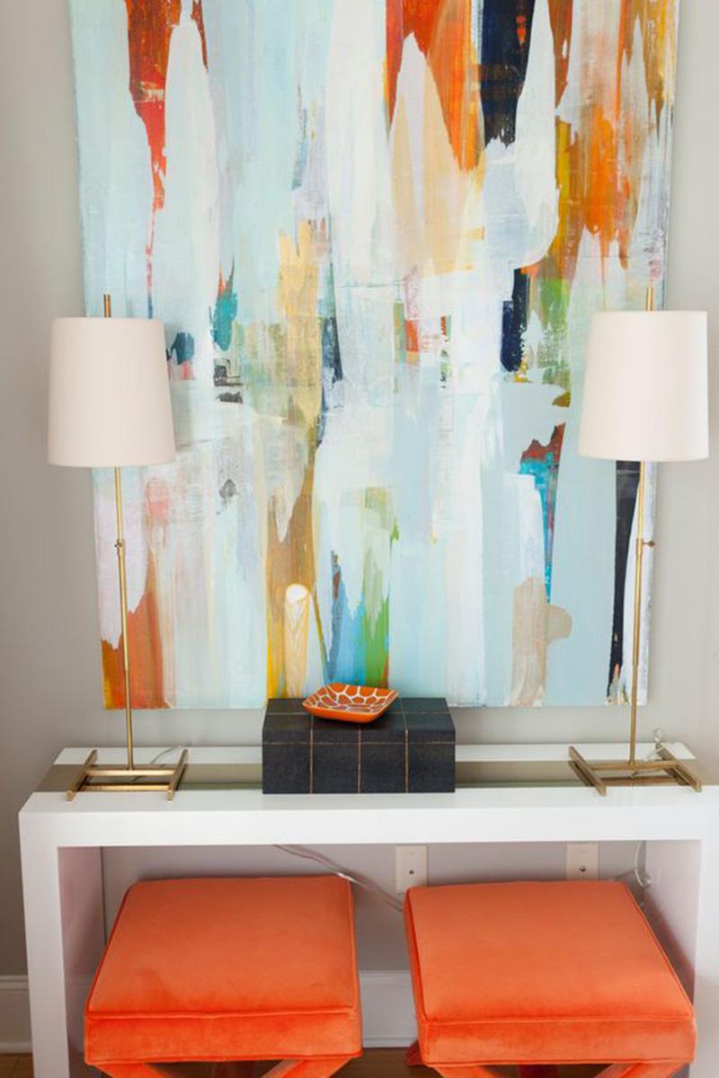 Fehér konzolasztal némi naranccsal és egy szuper jó festménnyel.