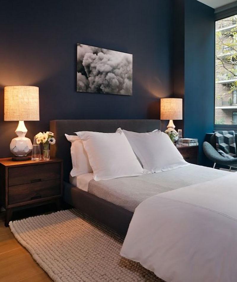 Kék, szürke, fehér plusz egy kis dió éjjeli szekrény. A világos színű kiegészítők, vagyis a lámpa, az ágynemű és a szőnyeg finomítják a fal és az ágy sötétségét.