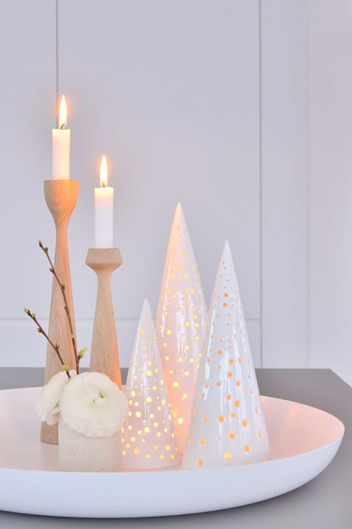 Different wooden and ceramic candle holders in light colors.