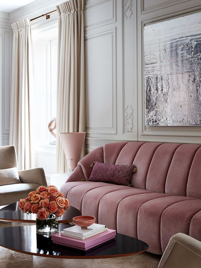 This pink, elegant sofa looks amazing with the natural colors and the dark coffee tables.