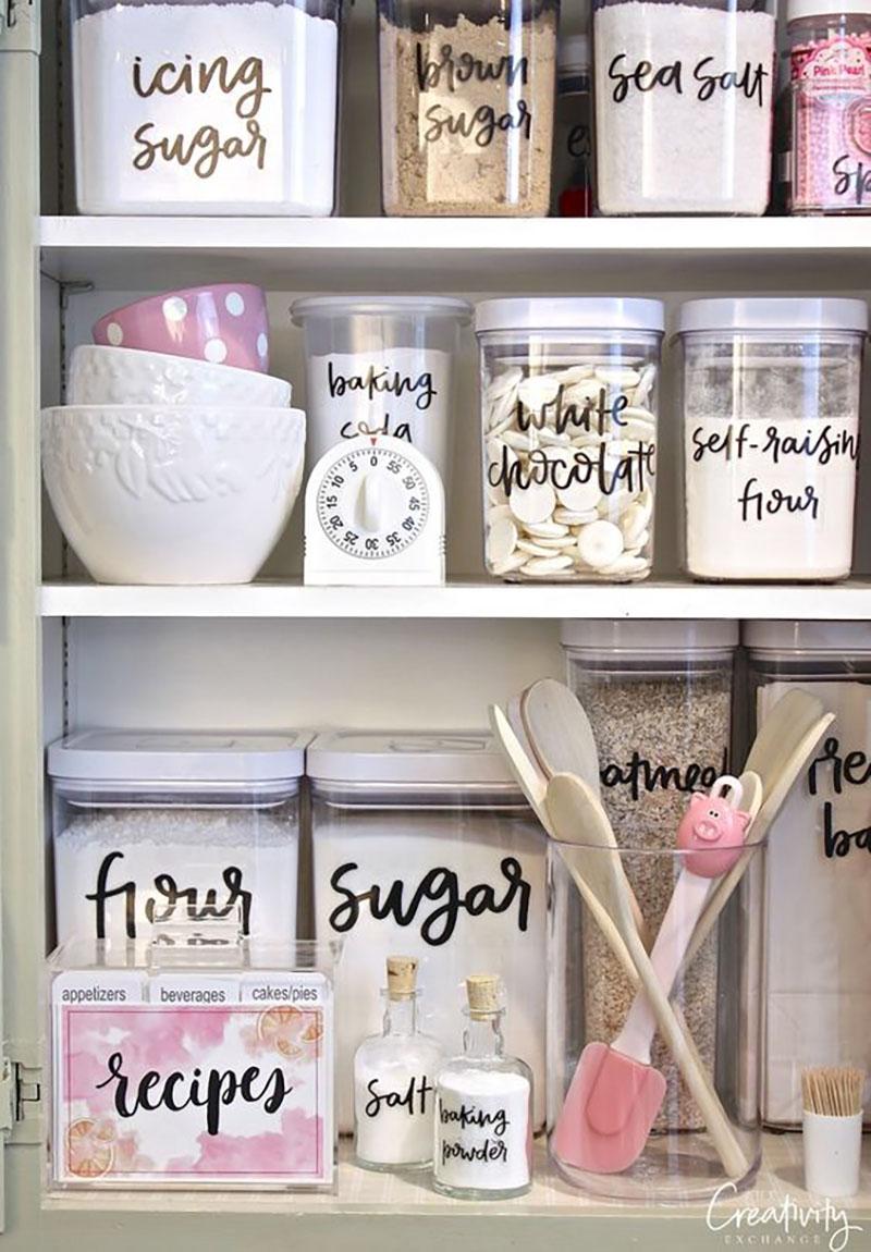 Konyhaszekrény vagy kamra rendszerezése feliratokkal, fehérben és rózsaszínben.