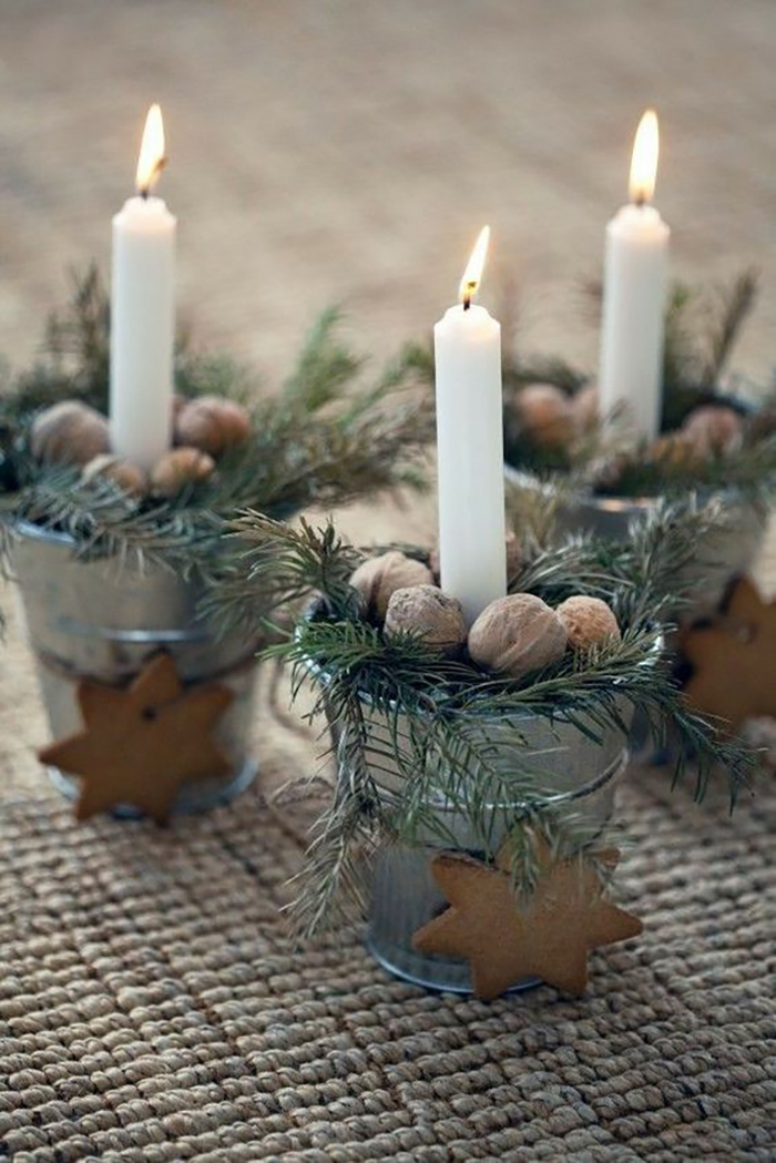 Gingerbread decoration on candle holders with nuts and pine branches.
