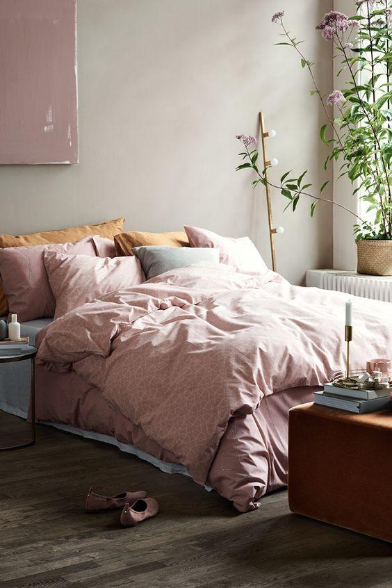 Natúr színű fal rózsaszín kiegészítőkkel és egy rozsdabarna puffal.