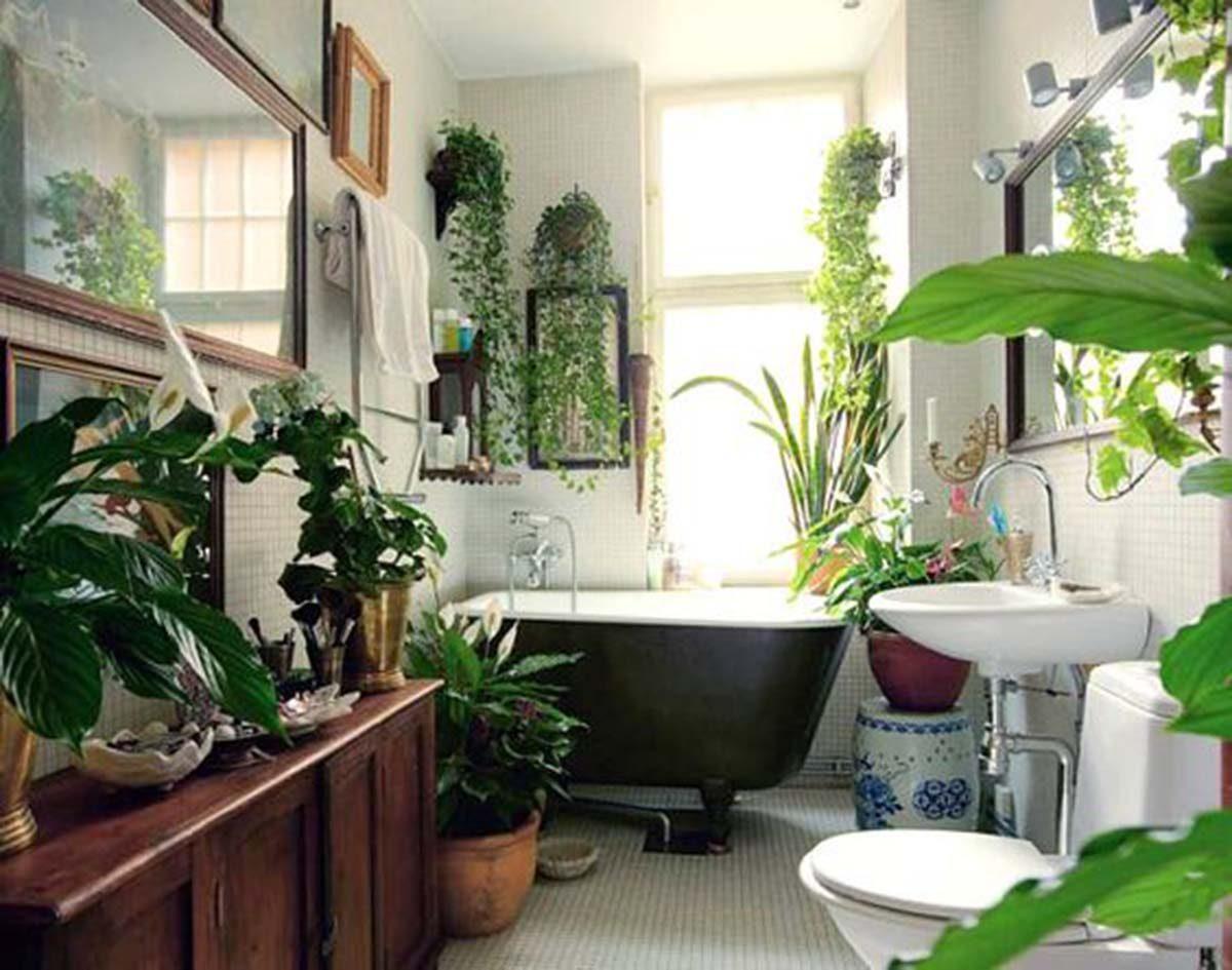 Fürdő dzsungel kivitelben, rengeteg növény, fa bútor és fehér. Remekül illik a zöld kád is ide.