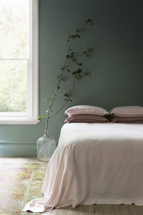 Green wall with pale pink bed linen, simple but a lovely combination.