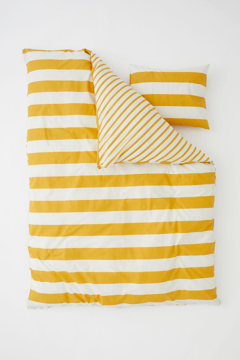 Sárga-fehér csíkos ágynemű, és milyen vagány, hogy a 2 oldalán különböző vastagságúak a csíkok (H&M Home).