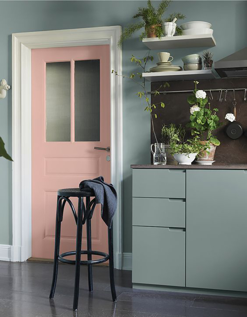 A pink door is unusual but why not? Add green kitchen cabinets and green wall color to that and this all will look unique.